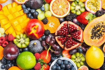 Wall Mural - Delicious healthy fruit background mango papaya strawberries oranges passion fruits berries, top view, selective focus