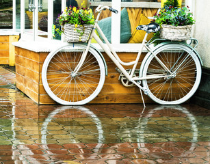 Photo sur Aluminium Velo White vintage bicycle with floral baskets standing outside at cafe background. Retro style transport with beautiful flowers