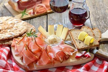 Südtiroler Bauernspeck mit Kren und reifem Bergkäse, dazu Landbrot sowie Rotwein – Typical South Tyrolean snack with bacon, horseradish, mountain cheese and farmhouse bread, served with red wine