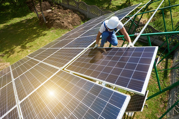 Risky work: mounting solar batteries on green metallic carcass. Environment friendly, green energy. Modern solution for natural resources saving, using renewable solar energy. New high-tech exterior.
