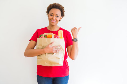 Young african american woman holding paper bag full of fresh groceries pointing and showing with thumb up to the side with happy face smiling