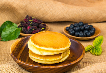 Fototapete - Pile of pancake in wooden bowl with mulberry and blueberry in wooden plate