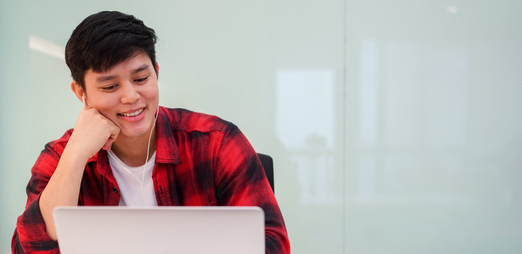 close up young asian man wearing earphone and watching media on web in relax time