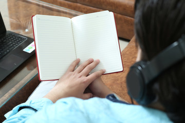 Man is holding diary in hand and listening music with headphone.