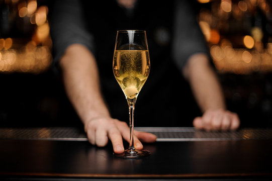 Close shot of glass with sparkling wine in the bartender's hands