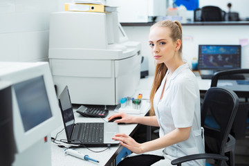 Modern technology in science. Scientist entering data of analysis or research results to laptop at laboratory.