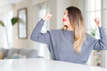 Young beautiful woman wearing winter sweater at home showing arms muscles smiling proud. Fitness concept.
