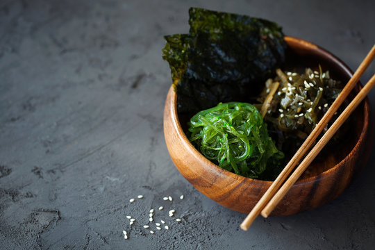 Traditional Japanese Snack - Chuka Wakame seaweed salad and crispy roasted nori sheets in wooden bowl on dark background top view with copy space for text.Healthy seafood high in vitamins