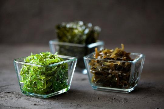 Traditional Japanese Chuka Wakame seaweed salad and crispy roasted nori sheets in glass bowl on dark background close-up.Asian japanese chuka. Organic natural product.Raw,vegan,vegetarian food
