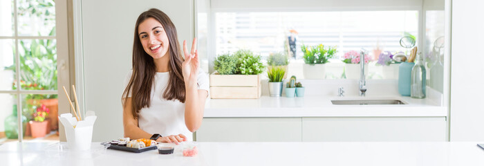 Wide angle picture of beautiful young woman eating asian sushi from delivery smiling looking to the camera showing fingers doing victory sign. Number two.