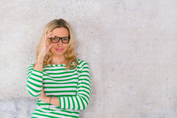 young, pretty blonde woman posing in front of a concrete wall and wearing green, white striped sweaters