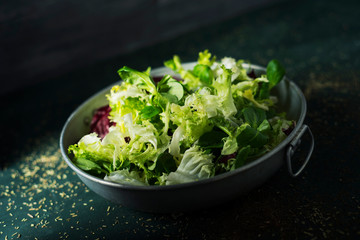 mix of different salad leaves in a metal dish