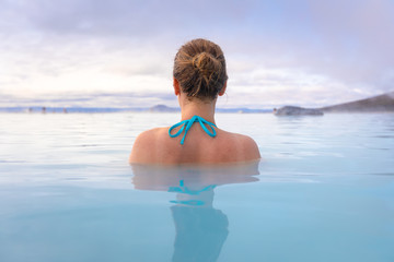 Geothermal spa in Iceland with young woman enjoying bathing in hot thermal pool with hotspring water for wellness and skin treatment, icelandic experience Fototapete
