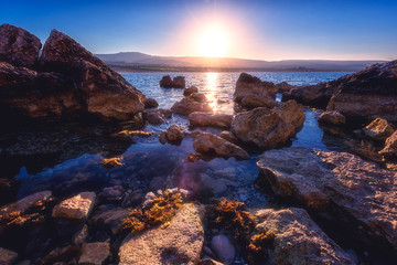 Amazing nature seascape with rising sun over the rocky seacoast of Akamas peninsula, Cyprus. Mediterranean sea near the popular Lara beach tourist location, travel background Wall mural