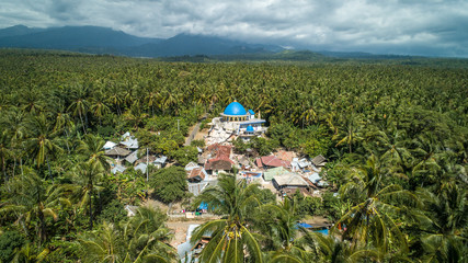 Aerial view of destroyed village and mosque in middle of a jungle surrounded by tropical palm trees in Lombok, Indonesia – Emotional Picture – Earthquake aftermath in south east Asia - Image