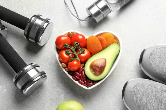Heart shaped bowl with healthy products and sports equipment on grey background, flat lay