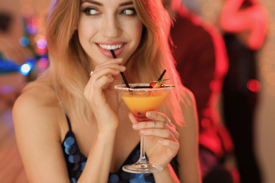 Beautiful young woman with glass of martini cocktail at party
