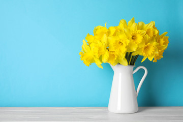 Bouquet of daffodils in jug on table against color background, space for text. Fresh spring flowers