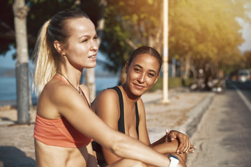 Wall Mural - Two fit friends sitting in the sun before working out