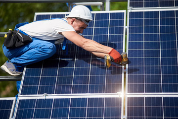 Professional technician installing solar panel to metal platform using screwdriver. Exterior solar system installation, renewable green energy generation concept.