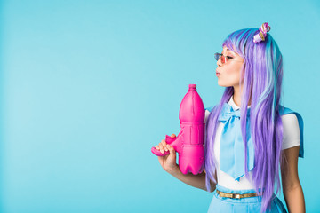 Asian anime girl in wig and glasses holding water gun isolated on blue