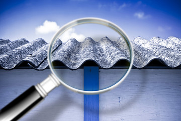 Analysis of the compounds of a dangerous asbestos roof - concept image with magnifying glass