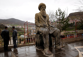 Men stand next to a statue of the Kurdish tribal leader Seyit Riza in Tunceli