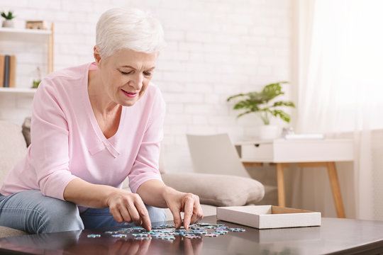 Elderly woman sitting at table and sorting jigsaw puzzle pieces
