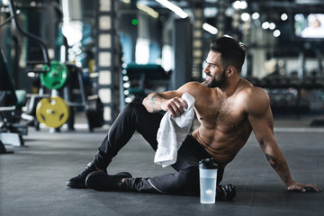 Handsome young muscular sportsman resting after workout