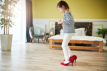 Little girl dressing up, wearing mother's red high heels
