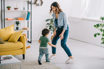 Full length view of smiling woman with son in living room