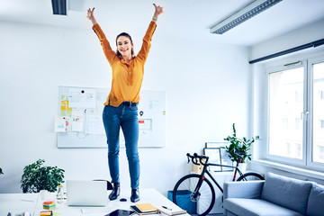 Happy young businesswoman cheering in office standing on desk