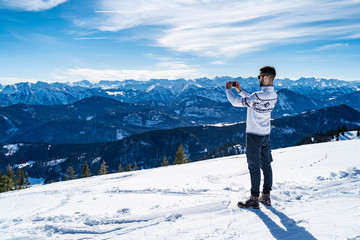 Germany, Bavaria, Brauneck, man in winter in the mountains taking a picture