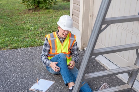 Injured architect sitting on the ground after having fallen off a ladder.