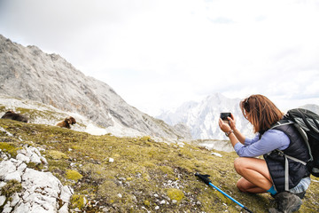 Austria, Tyrol, woman on a hiking trip in the mountains taking cell phone picture