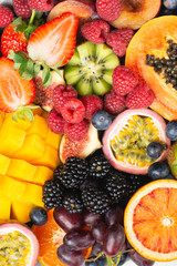 Wall Mural - Delicious fruit background mango papaya oranges passion fruits berries, overhead view, selective focus, copy space