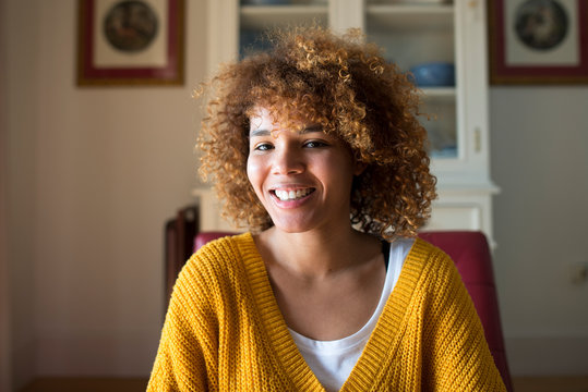 Portrait of smiling young woman with curly hair at home