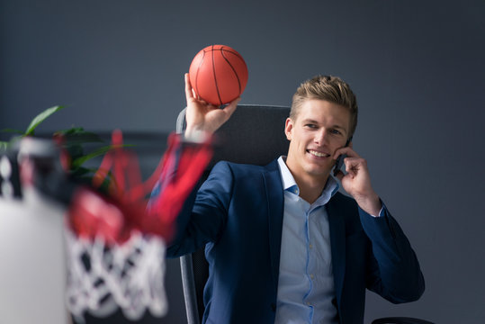 Young businessman sitting at desk in office playing basketball and talking on cell phone