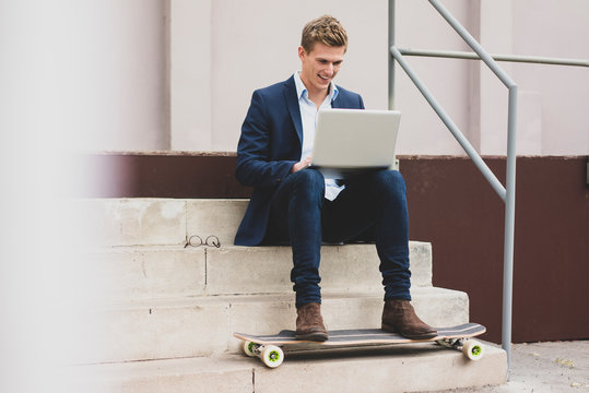 Happy young businessman with skateboard sitting outdoors on stairs using laptop