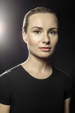 Portrait of blond woman in front of black background