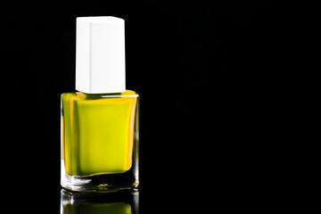 Lime green neon nail polish in bottle isolated glossy black background, copy space, selective focus