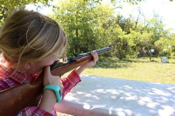 Girl aiming to shoot at target