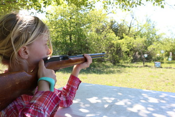 Girl with blond hair doing target practice with a 22 rifle