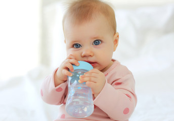 Charming baby 9 months old sitting on the bed in pink clothes with a bottle of water