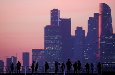 """People gather at a view point with Moscow International Business Center, also known as """"Moskva-City"""" in the background during sunset in Moscow"""
