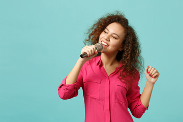 Portrait of smiling african girl in casual clothes dancing sing song in microphone isolated on blue turquoise wall background in studio. People sincere emotions, lifestyle concept. Mock up copy space.