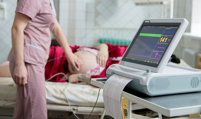 Pregnant woman with electrocardiograph check up for her baby. Fetal heart monitoring. Diagnostic, healthcare, medical service