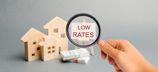 A magnifying glass is looking at a poster with the word Low rates and wooden house. The concept of reducing interest rates on mortgages. Housing on credit. Rents. Real estate capitalization. Insurance