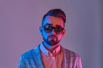 Portrait of attractive pensive man in checkeret blazer and sunglasses. Red and blue lights.