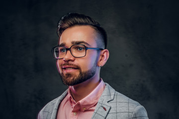 Portrait of young smiling man in checkered blazer, pink shirt and glasses